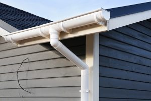 Gutter cleaning in Monroe, white gutter downspout and elbow on blue house