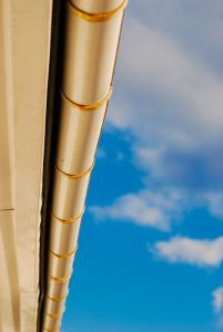 Gutter cleaning in South River, underside picture of pale yellow gutter on pale yellow house with a blue sky background with clouds